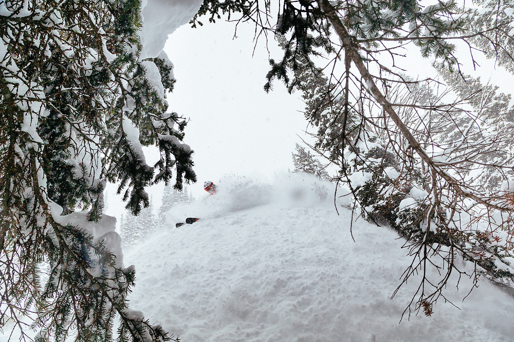 Andrew Whiteford sets off a mini avalanche onto his photographer Jay Goodrich during a shooting in the side-country near JHMR.
