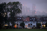 Residential high-rise towers in the distant metropolis and a setting sun behind the ash trees that form one side of Ruskin Park in Lambeth, on 4th July 2021, in London, England.