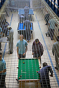 Prisoners play pool and socialise during a recreation period on C wing at the Young Offender Institution, Aylesbury, United Kingdom.