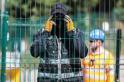 Harefield, UK. 22 July, 2020. A masked HS2 security guard observes a press photographer during works for the HS2 high-speed rail link close to Harvil Road. Environmental activists from HS2 Rebellion and Stop HS2 continue to protest against HS2, which is currently projected to cost £106bn and will remain a net contributor to CO2 emissions during its projected 120-year lifespan, from a series of wildlife protection camps along its route.