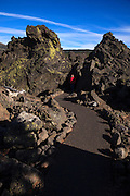USA, Oregon, Mt. McKenzie Pass Scenic Byway,  hiker on River of Lava Trail passing between very large lava rocks. MR