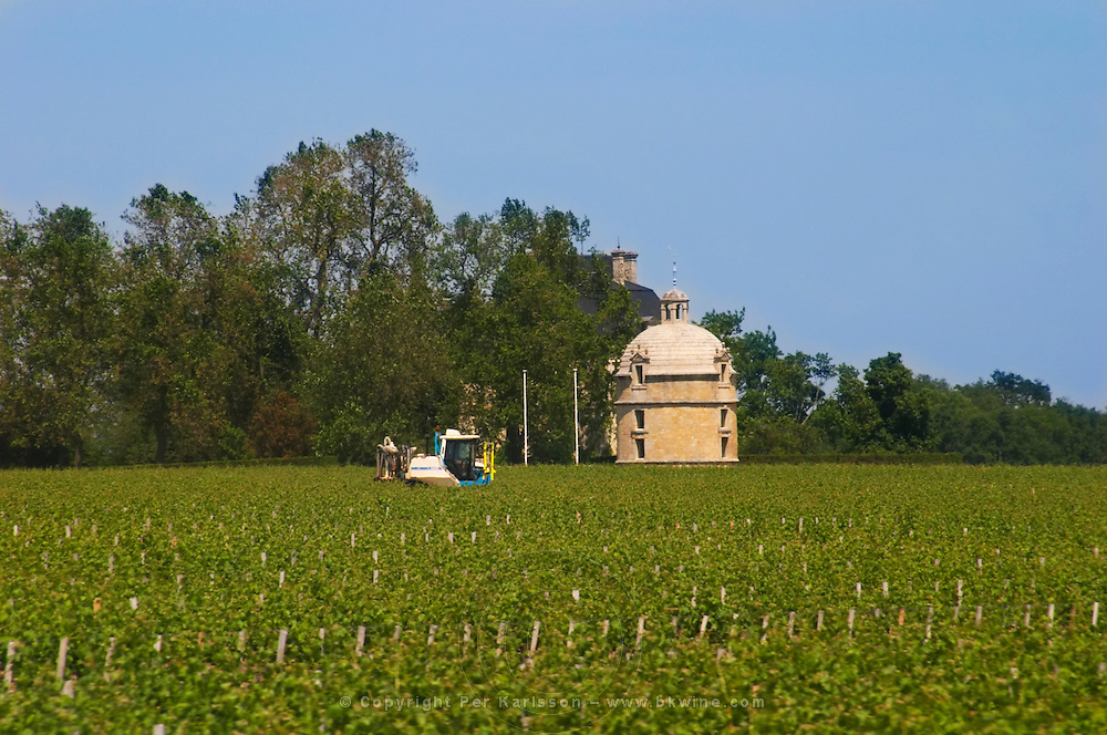 A view over the vineyard of Chateau Latour with the tower and the chateau and a tractor working the soil, Pauillac, Medoc, Bordeaux Pauillac Medoc Bordeaux Gironde Aquitaine France