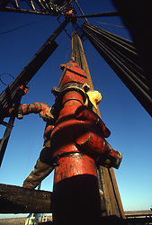 Stock photo of roughneck working on drill floor of oil and gas rig in West Texas.