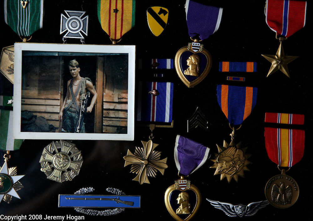 Ron Klus, a Loach door gunner, in B Troop, 1st Squadron, 9th Cavalry, 1st Cavalry Division is seen in a photograph made in 1969 at Quan Loi, Vietnam. Klus is surrounded by the decoration he earned during his service which led to his suffering with PTSD until his death in 2007.