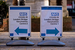 © Licensed to London News Pictures. 22/01/2021. LONDON, UK. Signs outside the London Bridge Covid-19 Vaccination Centre.  The latest data according to the Government Office for Science and the Scientific Advisory Group for Emergencies (Sage) suggests that the reproduction number, or R value, of Covid-19 transmission has fallen and is now estimated to be between 0.8 and 1 across the UK..  Photo credit: Stephen Chung/LNP