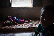Siblings rest in their living room during the afternoon heat in the village of Basheria, northwestern Syria. Idlib province in Syria's northwest is one of the few areas in Syria which is currently under FSA control, although this control is patchy and ever shifting. 20/06/2012