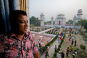 Ahsanullah Moni, millionaire film director and business man, stands on the balcony of a hotel overlooking his new Taj Mahal Bangladesh, a replica of India's famed Taj mahal built in the middle of rice fields near his home village outside Dhaka, Bangladesh.  He says he built it because most  Bangladeshi people cannot afford the trip to Agra, India to see the real thing. The entry fee for his replica is 50 Taka, about  .75 USD. There is a 25-room hotel facing the Bangla Taj and he says his plans include a film studio and center nearby. The construction of the main Taj will be completed in about a month but the tourist attraction is now open to the public. Moni claims about 20,000 people visit daily. There is only a single lane two kilometer road winding through the surrounding rice fields connecting the main road to his attraction, near the town of Sonargaon, about 30 kilometers from Dhaka.