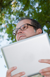 Mature man with digital tablet, looking away