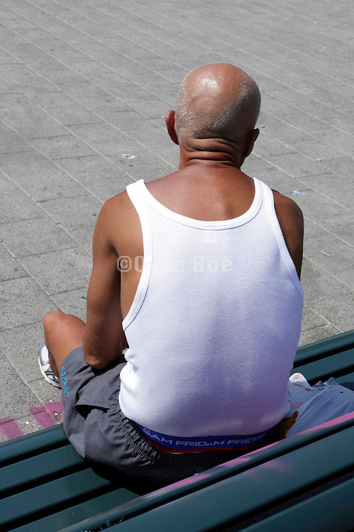 sun browned man sitting on a bench