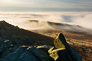 A stunning temperature inversion as viewed from Higger Tor in the Peak District National Park. Carl Wark, site of an Iron Age Hill Fort, is partially enshrouded in mist whilst the Derwent Valley beyond is completely obscured. Autumn in Derbyshire, England, UK. October 2014.