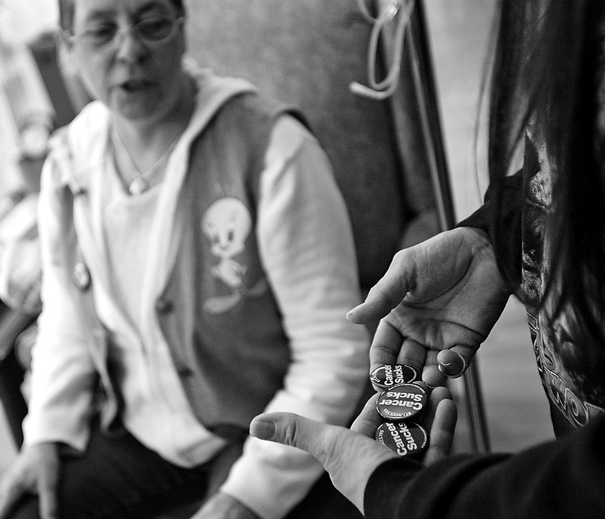 """Marie shows Annie Baranik, the sister of a cancer patient, pins that read """"Cancer Sucks"""" as she waits for her chemo treatment on March 23, 3007 at the Harold Leever Cancer Center in Waterbury."""