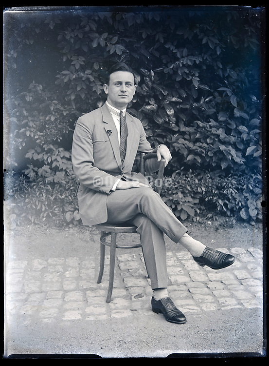 portrait of an adult man sitting on a chair in garden setting circa 1930s