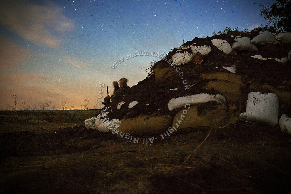 Soldiers near trenches are standing guard at night, while listening to the enemy's shelling, ready to run for cover if being targeted, on the frontline of Hranitne, near Mariupol, southeast Ukraine.