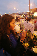 Esther Bekerman prays and lights a candle outside the Kosher supermarket where a family member was wounded the day before<br />