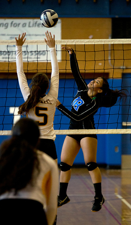 Encinal's Kaleena Ugaitafa (18) taps the ball back over Alameda blocker Phoebe Brand (5) during the first set of a girls' high school volleyball match, Thursday, Sept. 17, 2015, at Encinal High School in Alameda, Calif. (D. Ross Cameron/Bay Area News Group)