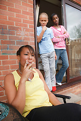 Mother smoking with disapproving children behind her