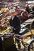 Amish boy plays on a carriage during the Annual Mud Sale to support the Fire Department  in Gordonville, PA.