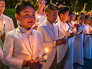12 AUGUST 2016 - BANGKOK, THAILAND: A Thai children's choir performs with candles on the Queen's Birthday. Thais celebrated the Queen's birthday Friday. Queen Sirikit of Thailand, was born Mom Rajawongse Sirikit Kitiyakara on 12 August 1932. She married  Bhumibol Adulyadej, King of Thailand (Rama IX) in 1950. He is the longest serving monarch in the world and she is longest serving consort of a monarch. Her birthday, like the King's Birthday (which falls on Dec. 5),  is a national holiday in Thailand. Her birthday, August 12, is also celebrated as Mother's Day in Thailand.      PHOTO BY JACK KURTZ