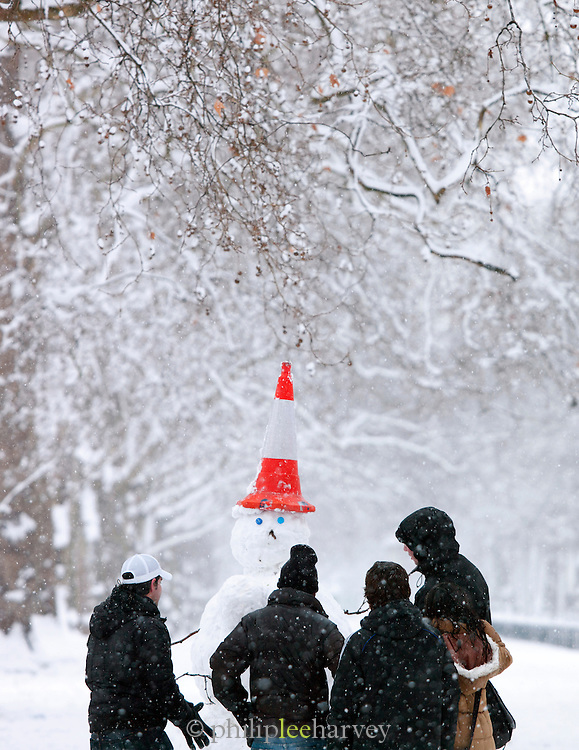 A group of people make a snowman with a traffic cone on his head in St James Park, London, UK