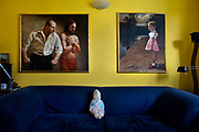 Bubble wrapped doll overlooked by 2 oil paintings in an artistic house in London, United Kingdom.