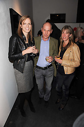 Left to right, IMOGEN ROBARTES and PEREGRINE & CAROLINE ARMSTRONG-JONES at a private view of photographs by Guido Mocafico entitled 'Guns and Roses' held at Hamiltons Gallery, 13 Carlos Place, London W1 on 21st January 2010.