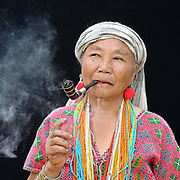 Portrait of a Karen Pwo ethnic minority woman smoking a pipe at Mae Lay village, Chiang Mai province, Thailand