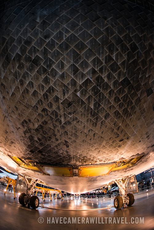The heat shield on the underbelly of the Space Shuttle Discovery at the Smithsonian National Air and Space Museum's Udvar-Hazy Center. Located near Dulles Airport, the Udvar-Hazy Center is the second public facility of the Smithsonian's National Air and Space Museum. Housed in a large hangar are a multitude of planes, helicopter, rockets, and space vehicles.