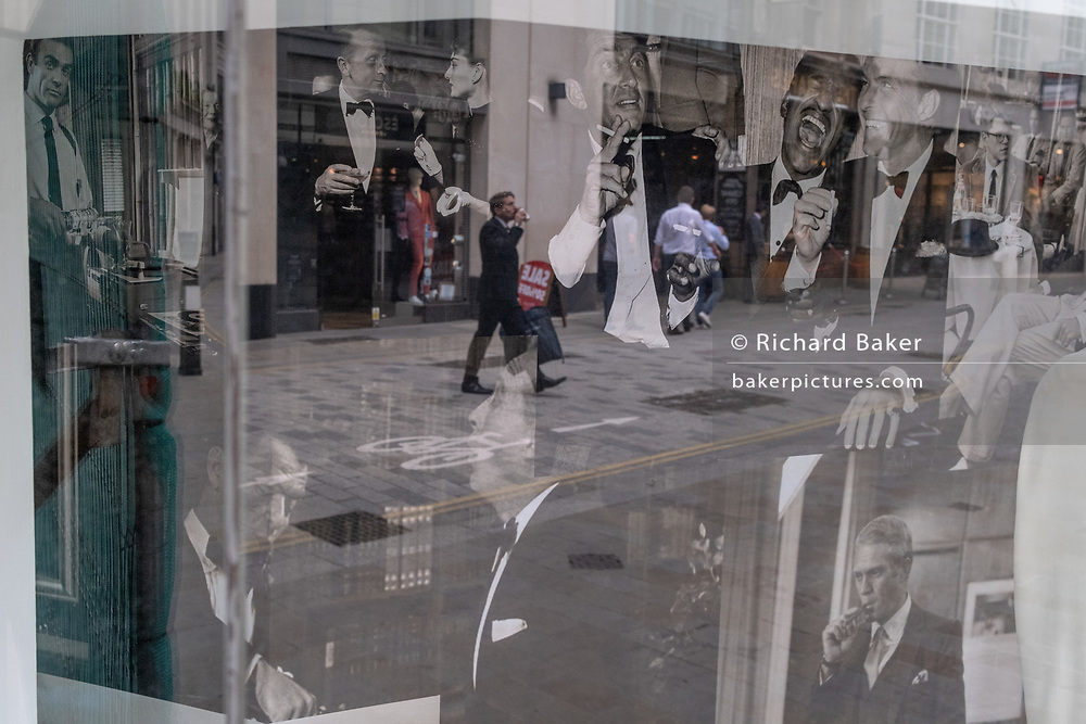 Merging with party images of the Rat Pack in the window of a menswear outfitters, are the reflection of a City worker taking a drink during the summer heatwave in Lime Street in the City of London, the capital's financial district, on 6th August 2020, in London, England.