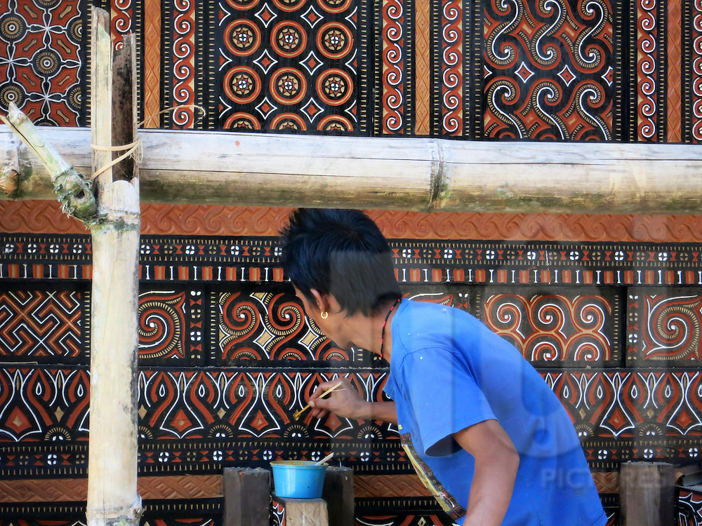 A local man paints intricate patterns on wood, Tana Toraja Regency, South Sulawesi, Indonesia, Southeast Asia