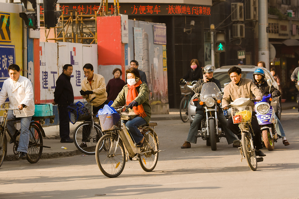 Shanghai, China, Asia - Woman riding a bicycle with face mask in the chaotic traffic of Shanghai.