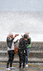 (c) Licenced to London News Pictures 21/03/2015. Scarborough, North Yorkshire, UK. (l-r) Malgorzata Zielinska, Agata Smith and Karolina Zieconka take a selfie with a wave. High tide brings huge waves to the shore at Scarborough. Photo credit : Harry Atkinson/LNP