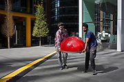 Pop-up catering workers carry a red oven cover alongside a yellow line covering hazardous electrical cabling at Leadenhall in the City of London, (aka The Square Mile) the capital's financial district, on 2nd September 2019, in London, England.