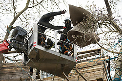 Steeple Claydon, UK. 23 February, 2021. National Eviction Team climbing bailiffs acting on behalf of HS2 Ltd use a cherry picker to dismantle a tree house during an operation to evict activists opposed to the HS2 high-speed rail link from ancient woodland known as Poors Piece. The activists created the Poors Piece Conservation Project there in spring 2020 after having been invited to stay on the land by its owner, farmer Clive Higgins. Already, local village communities have been hugely impacted by HS2, with 550 acres of land seized including a large section of a nature reserve.