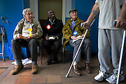 As a man on crutches hobbles past, three tellers from the main political parties check the addresses of voters in Herne Hill Methodist Church SE21 that serves as a temporary Polling station for voters on Britain's general election day. Their job is to record the election numbers of those about to vote, making sure that their political colleagues don't drop more literature in to that address, now that the occupants have voted.
