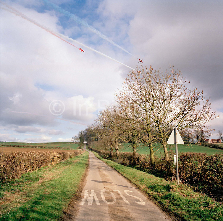 Hawk jets of the Red Arrows, Britain's RAF aerobatic team perform training display over the skies above their Lincolnshire home. Their winter training flight takes them over Brattleby Hill just outside the perimeter fence of their base at RAR Scampton. But ironically, the word Slow has been stencilled on this quiet road though the Hawk jets fly up to 500mph. During their training period, they fly up to 6 times daily, when weather permits, learning new manoeuvres.