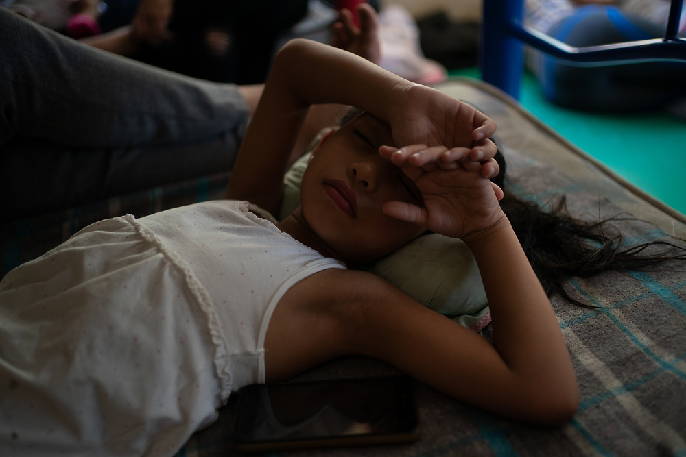 In a migrant shelter in Tapachula, Mexico, a girl rests on a bunk. Her mother has applied for permission to stay in Mexico and they await a response from the Mexican authorities.