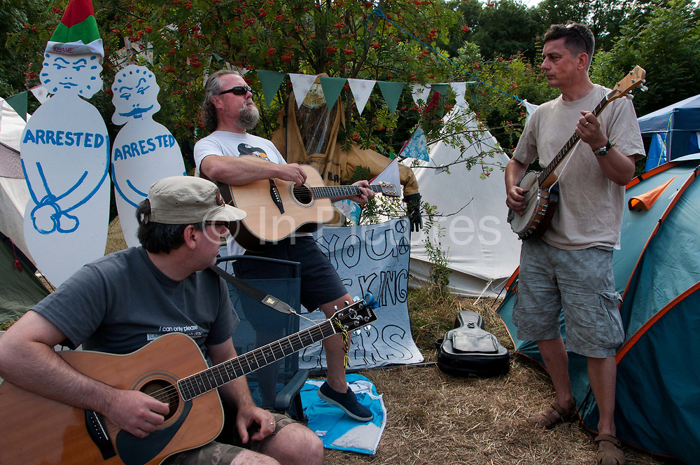 Balcombe, West Sussex. Site of Cuadrilla drilling . Roadside camp of protesters. A trio of musicians sing protest songs in front of cardboard cutout figures of arrested protesters.
