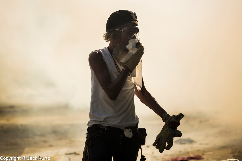 02 DECEMBER 2013 - BANGKOK, THAILAND: An anti-government protestor walks through a cloud of tear gas in Bangkok. The protestors use the water to rinse tear gas out of their eyes. Anti-government protestors and Thai police continued to face off Monday for a second day. Police used tear gas, water cannons and rubber bullets against protestors who charged their positions near the barriers on Chamai Maruchet bridge on Phitsanulok Road, which leads to the Government House.     PHOTO BY JACK KURTZ