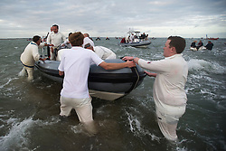 © London News Pictures. 17/09/2012. Southampton, UK.  Cricketers boarding a boat after the match. Teams play a cricket match on the Bramble Bank in the middle of The Solent on September 17, 2012.  The annual cricket match between the Royal Southern Yacht Club and The Island Sailing Club, takes place on a sandbank which appears for 30 minutes at lowest tide. The game lasts until the tide returns. Photo credit : Ben Cawthra/LNP.