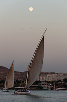 Egypt. Aswan stands on the east bank of the Nile. A felucca is a traditional wooden sailing boat, with the moon as background.