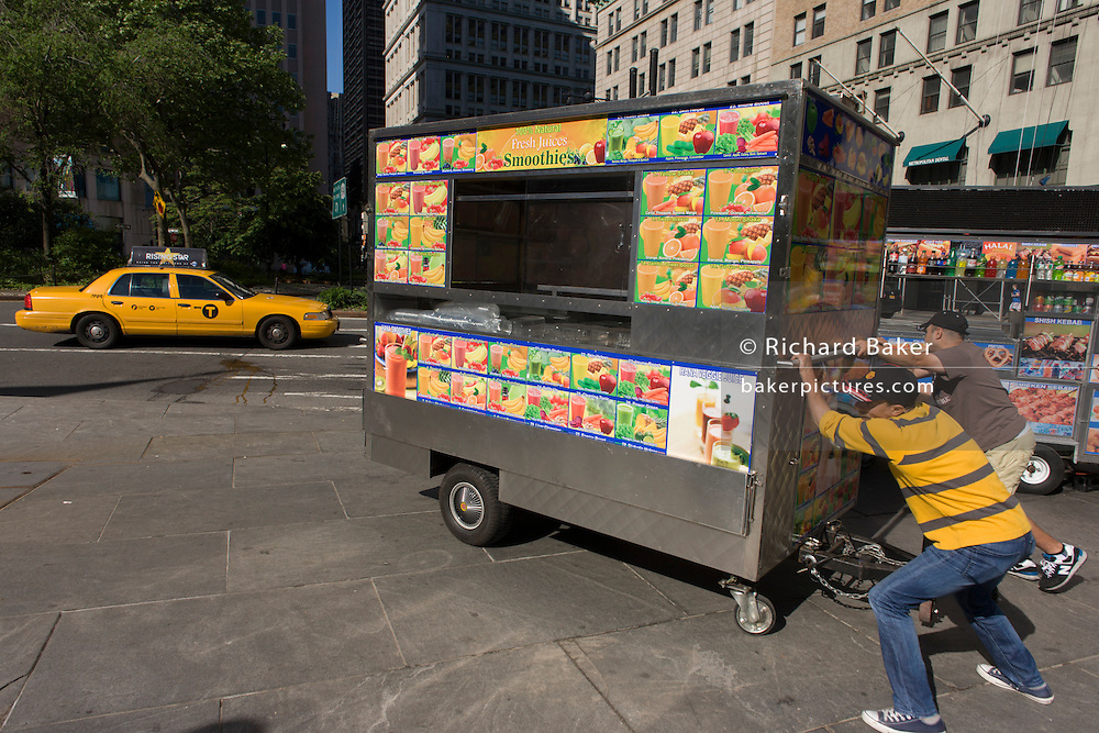 Pushing into position a kiosk selling multiple varieties of Smoothie fruit drinks on sale on Broadway, New York City. i