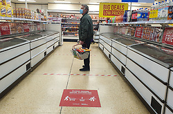 © Licensed to London News Pictures. 28/03/2020. London, UK. A shopper observes social distancing in Iceland supermarket in north London after UK Government ordered a lockdown to slow the spread of the coronavirus. Photo credit: Dinendra Haria/LNP