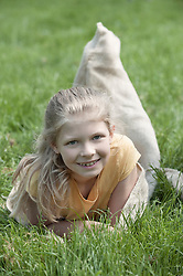 Girl in a sack lying on meadow after sack race and smiling, Munich, Bavaria, Germany