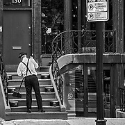 Along Boston's Newbury Street.  This gentleman is sweeping the steps up to his hat store.  I thought that the hat boxes along the stairs make a very interesting accent in letting people know where the stairs lead.  Of course, he is demonstrating his product the whole time.