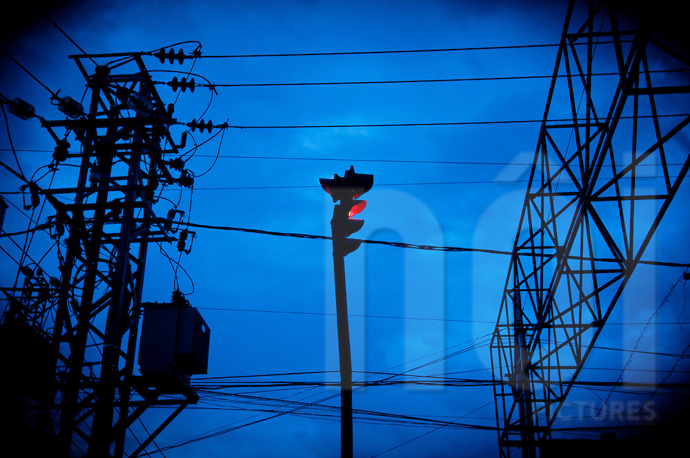 Red traffic light surrounded by electric cables and pylons with a dramatic dark blue sky in background, Nha Trang, Vietnam, Southeast Asia