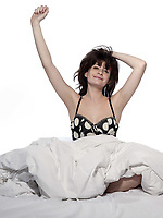 young woman in bed awakening tired insomnia hangover  in a white sheet bed on white background