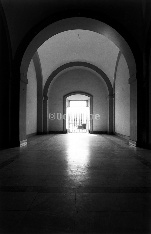 Empty hallway with a chair in the doorway.