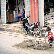 A young boy helps repair a pot-hold in the street in Phonsavan in northeastern Laos, capital of Xieng Khouang Province and a central town in the Plain of Jars. The people of the region are predominantly of Hmong ethnicity.