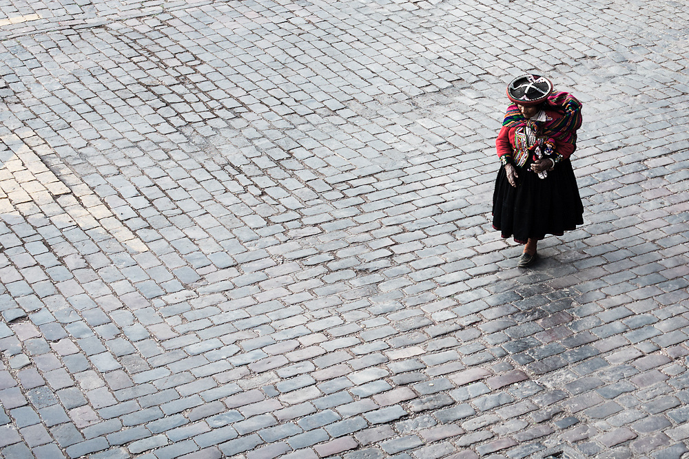 A birds eye view of a peruvian women dressed in bright traditional cothing as she walks along the coble stone streets in the Plaza de Armas in Cusco, Peru.