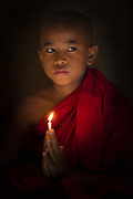 A novice monk lit by a candle in Myanmar.